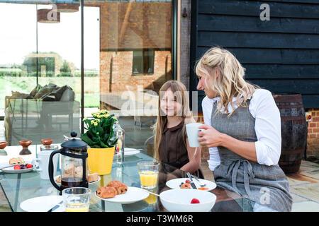 Kaukasische Mutter und Tochter mit Frühstück im Hinterhof - Stockfoto