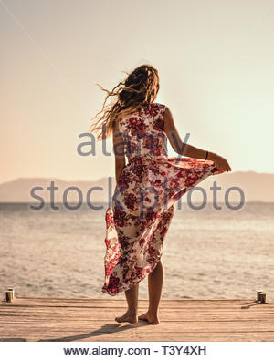 Frau Stehen auf einem Bein in Weiß und Rot mit Blumenmuster ärmelloses Kleid - Stockfoto