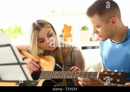 Tausendjährigen Frau und Gitarre Lehrer Musik wiedergeben - Stockfoto