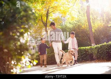 Glückliche junge Familie wandern ihren Hund - Stockfoto