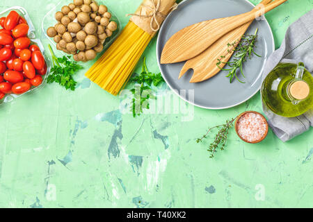 Spaghetti, shimeji Pilze, Tomaten, Olivenöl, rosa Salz, leer Keramik Schüssel, Kochlöffel für Salat über grüne konkrete Textur Hintergrund. Top - Stockfoto