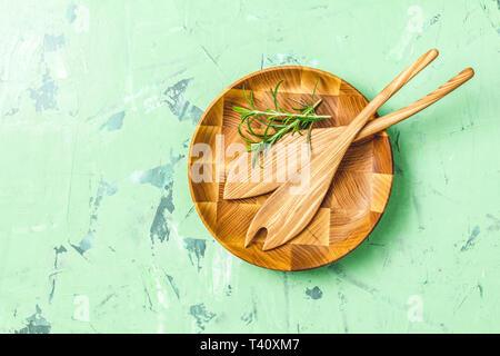 Kochlöffel für Salat in hölzerne Platte über grüne konkrete Textur Hintergrund, gesunde Ernährung Konzept, Ansicht von oben, kopieren Sie Text. - Stockfoto