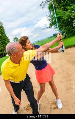 Golf Training mit Pro im sandbunker - Stockfoto