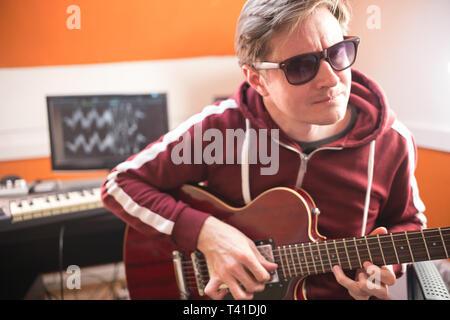 Ein Mann in Gläsern, Gitarre zu spielen und mit der Aufnahme eines Songs im Studio - Stockfoto