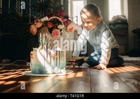 Kleinkind Junge sitzt auf dem Boden in der Nähe der Torte auf dem Hintergrund der Blumen. - Stockfoto