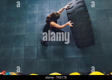 Passform weiblichen Athleten, mit einem riesigen Reifen, drehen und in der Turnhalle durchführen. Frau Trainieren mit großen Reifen. - Stockfoto
