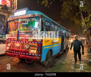 Horizontale Sicht auf einen öffentlichen Bus hinunter die Straße in Kalkutta aka Kalkutta, Indien fahren. - Stockfoto