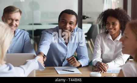 Lächelnd afrikanischen Manager handshaking Gruß kaukasischen Client Group Verhandlungen - Stockfoto