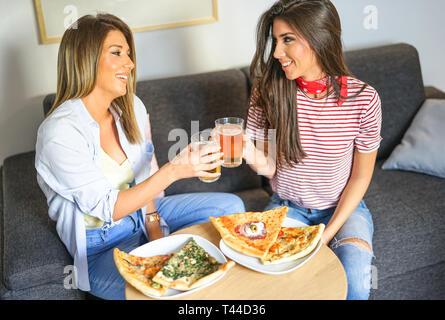 Junge Frauen mit einem gemeinsamen Mittagessen Toasten von Bier und essen Pizza - glückliche Freunde genießen ein Abendessen sitzen auf der Couch im Wohnzimmer zu Hause. - Stockfoto
