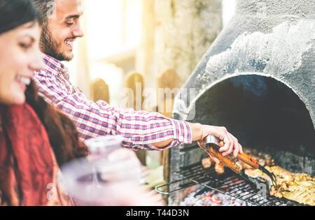 Glückliche junge Freunde machen eine Grillparty Grillen von Fleisch im Hinterhof - schöner Mann kochen gegrilltes Rindfleisch für seine Freunde. - Stockfoto