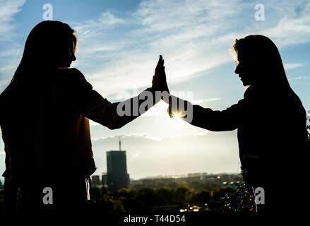 Silhouette von zwei jungen Frauen, die hohe fünf in schöne Gefühle auf einem Hügel bei Sonnenuntergang in einem Park im Freien mit der Stadt im Hintergrund stehend - Stockfoto