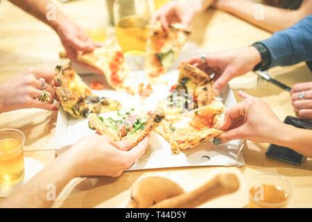 Nahaufnahme von Menschen die Hände unter diversen Scheiben köstliche italienische Pizza zu Hause - Gruppe von Freunden genießen Sie eine Mahlzeit essen Speisen und Getränken eingenommen werden - Stockfoto
