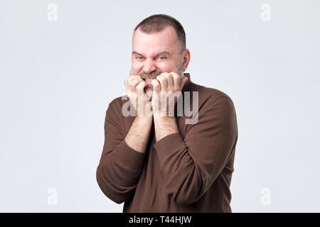 Mann mit Bart in braunes Hemd Beißen Nägel in Angst - Stockfoto
