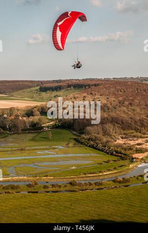 Seaford, East Sussex, Großbritannien. April 2019. Kälter Wind aus dem Osten bringt Gleitschirmflieger in den schönen South Downs mit Blick auf den Cuckmere River hoch und Drüben.