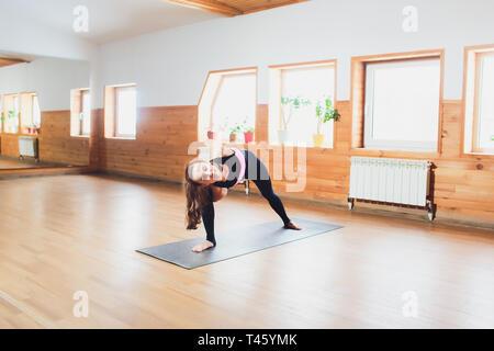 Ansicht der Rückseite des jungen weiblichen Yogi in Sport-BH und Leggings, gebunden die Gestreckte Flankendehnung darstellen, utthita parsvakonasana Baddha, beim Üben von Yoga - Stockfoto