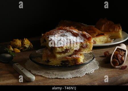 Traditionelle griechische Küche. Bougatsa, griescreme Gebäck gefüllt mit Sahne und Sultaninen, garniert mit Puderzucker. - Stockfoto