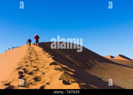 Personen oder Touristen klettern Düne 45 in Sossusvlei, Namib Naukluft National Park, Namibia, Afrika - Stockfoto