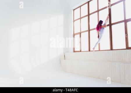 Schöne Frau Yoga und Akrobatik in der Nähe der grossen Fenster. - Stockfoto