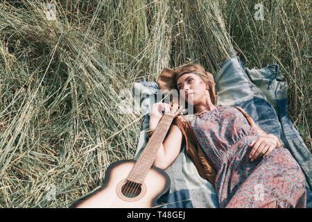 Schöne junge hippie Frau schlafen auf gemähtem Gras - Stockfoto
