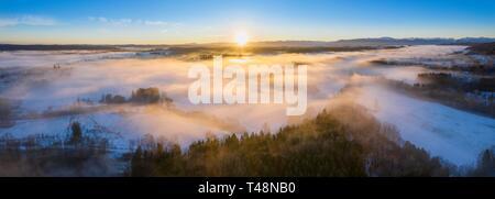 Sonnenaufgang über Wälder und Wiesen mit dem morgendlichen Nebel im Winter, auf der Rückseite Alpine Kette, in der Nähe von Geretsried, Tölzer Land, Drone, Alpenvorland - Stockfoto