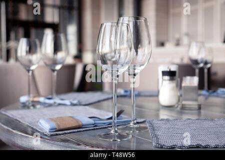 Restaurant Interieur, modernen Ambiente, Wein und Wasser Gläser, Gabeln und Messer auf Textil Servietten stehen in der Zeile auf Vintage Grau Holztisch. Konzept ba - Stockfoto