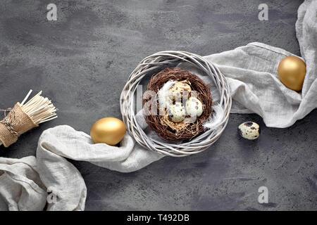 Ostern flach auf dunklem Hintergrund mit wachtel Eier im Nest, Bettwäsche fabrique und zwei goldene Eier auf dunkel strukturierten Hintergrund - Stockfoto