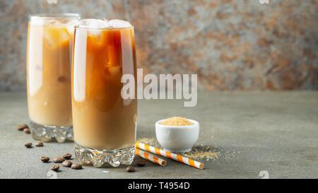 Eis Kaffee in ein hohes Glas mit Sahne über und Kaffeebohnen gegossen. Kalten Sommer trinken auf einem braunen Rusty Hintergrund mit Kopie Raum - Stockfoto