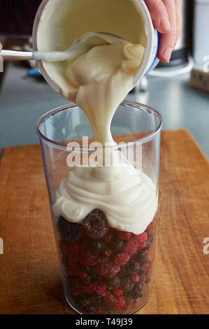 Frische Sommer Obst und Crème Fraiche mit einem Stabmixer hinzugefügt wird, eine Fruit Smoothie zu machen - Stockfoto