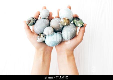 Hände, die stilvolle Ostereier auf weißem Holz- Hintergrund. Moderne und farbenfrohe Ostereier mit pastellfarbenen natürlichen Farbstoff in Marmor Farben bemalt. Happy Osten - Stockfoto