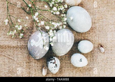 Stilvolle Ostereier mit Blumen auf rustikalen Stoff im sonnigen Licht auf Holz. Moderne und farbenfrohe Eier bemalt mit natürlichen Farbstoff in grauem Marmor. Gerne E - Stockfoto