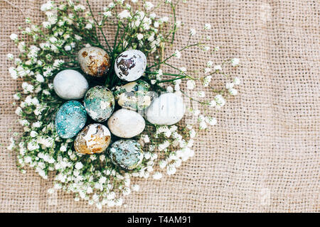 Stilvolle Ostern Wachteleier mit Frühlingsblumen in floralen Nest auf rustikalen Stoff im sonnigen Licht auf Holz. Moderne bunte Eier mit natürlichen Farbstoff in lackiert Stockfoto