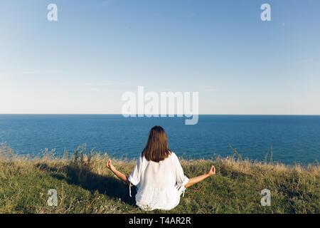 Junge schöne Frau Entspannung und Yoga am Strand, sitzen im Gras, Meditieren und hören von Wellen des Meeres. Hipster girl Yoga. Meditat - Stockfoto
