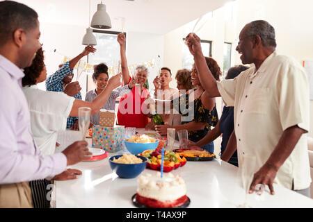 Tausendjährige schwarze Frau Champagner während drei Generation Familienfeier zu Hause gießen - Stockfoto