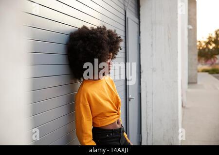 Junge schwarze Frau mit Afro in der Straße gegen Grau Sicherheit Rollläden schiefen, Seitenansicht - Stockfoto