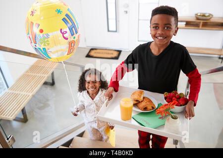 Portrait der Kinder, die ihre Eltern ein Frühstück im Bett auf Tray mit Ballon zum Geburtstag feiern. - Stockfoto