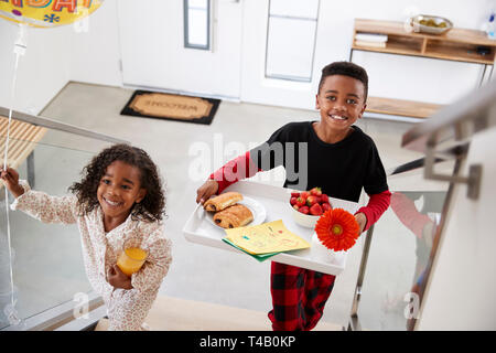 Kinder, die ihre Eltern ein Frühstück im Bett von Fach zu Geburtstag Muttertag Väter feiern Tag - Stockfoto
