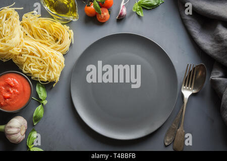 Leere schwarze Platte und Grenze der rohen Pasta, Tomaten im eigenen Saft, Basilikum, Parmesan zum Kochen italienische und mediterrane Gerichte. - Stockfoto