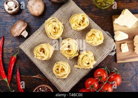 Ungekochte italienische pasta Tagliatelle in Form von Nestern einen Sack mit Gemüse - Stockfoto