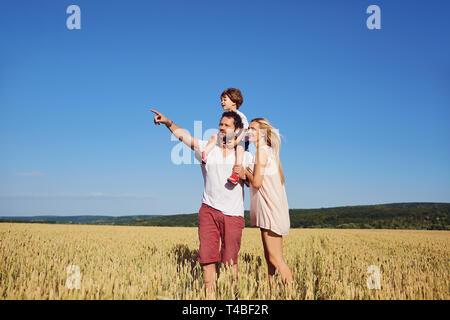 Eine glückliche Familie, die in einem Weizenfeld. - Stockfoto
