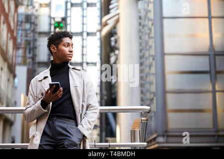 Modische junge schwarze Frau, die in der Stadt halten, Smartphone, niedrigen Winkel - Stockfoto