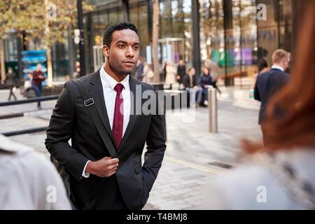 Junge schwarze Geschäftsmann zu Fuß in einer Straße in der Stadt, selektiver Fokus - Stockfoto