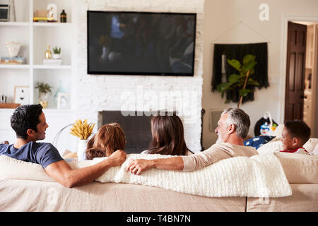 Zurück Blick auf drei Generation spanischer Familie auf dem Sofa fernsehen, Opa bei erwachsenen Sohn suchen - Stockfoto