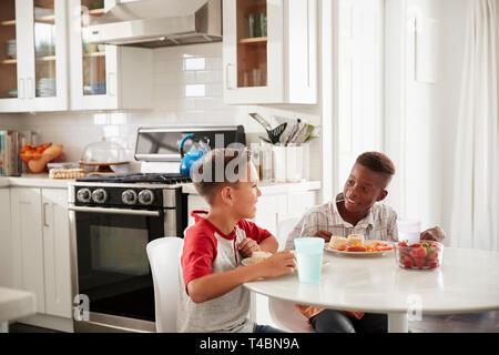 Zwei vor - jugendlich männliche Freunde sitzen im Gespräch in der Küche bei einem PLAYDATE an einem Boy's House