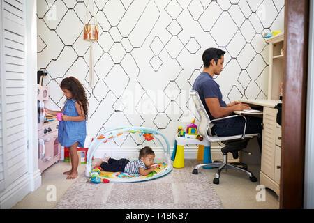 Papa sitzt an einem Schreibtisch arbeiten von zu Hause aus, während sein Sohn und Tochter spielen im Zimmer hinter ihm - Stockfoto