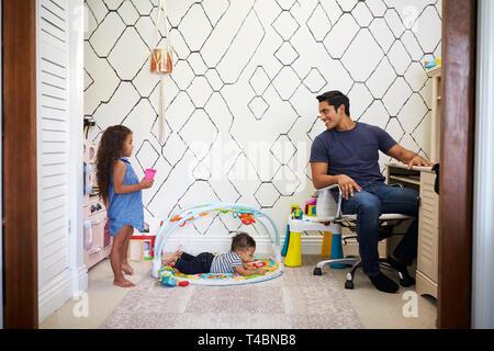 Vati am Schreibtisch zu Hause arbeitet, dreht sich um, um zu seinen jungen Kinder zu sprechen, spielen in den Raum hinter ihm - Stockfoto