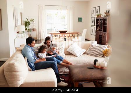Junger spanischer Familie sitzt auf dem Sofa, ein Buch lesen gemeinsam im Wohnzimmer, vom Eingang gesehen - Stockfoto