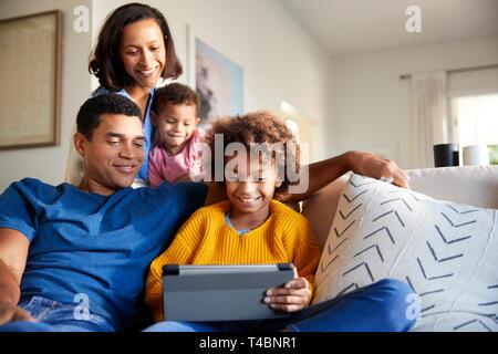 Junge Familie Zeit miteinander zu verbringen mit einem Tablet-PC in Ihrem Wohnzimmer, Vorderansicht - Stockfoto