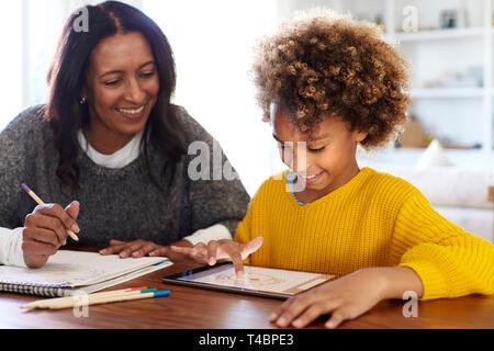 Gemischten Rennen junge Großmutter an den Tisch sitzen Hausaufgaben mit ihrer Enkelin über einen Tablet-PC, in der Nähe - Stockfoto