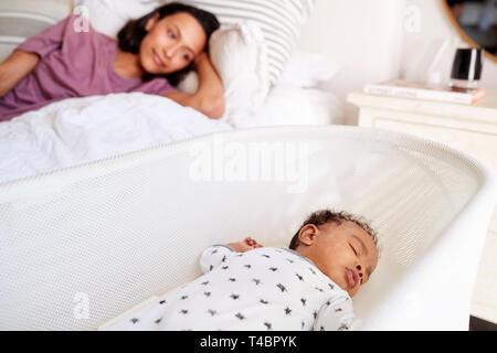Nahaufnahme von jungen Erwachsenen Mutter lag auf ihrem Bett, ihr drei Monate alten Baby schlafend in seinem Kinderbett - Stockfoto