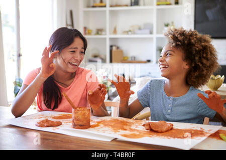 Zwei Freundinnen Spaß spielen mit Knetmasse zu Hause, lachen und zeigen Ihre schmutzigen Hände zueinander, in der Nähe - Stockfoto
